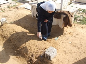 An orphan is watering the tomb of her father who was killed by an Israeli air-strike during the Gaza War
