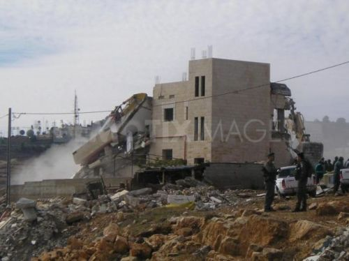 Israeli bulldozers demolishing Palestinian houses under the protection of the Israeli forces
