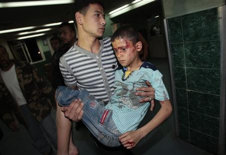 A wounded Palestinian boy is carried into Al-Shifa hospital following Israeli air strikes in Gaza
